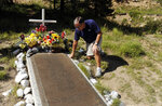 FILE - In this Aug. 27, 2010, file photo, John Yeros, a former member of the Wichita State football team, kneels next to a memorial near the site of an Oct. 2, 1970 plane crash that killed 31 persons in Silver Plume, Colo. Yeros was on the team, but not on the plane. Six weeks later, on Nov. 14, 1970, a plane carrying members of the Marshall football team crashed. As fate would have it, Marshall's first trip to the NCAA Tournament in 31 years means a date with Wichita State on Friday, March 16, 2018, in San Diego. (AP Photo/Chris Schneider, File)