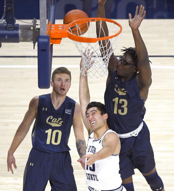 Utah State guard Abel Porter (15) shoots as Montana State guard Caleb Bellach (10) and forward Jubrile Belo (13) defend during an NCAA college basketball game Tuesday, Nov. 5, 2019, in Logan, Utah. (Eli Lucero/The Herald Journal via AP)