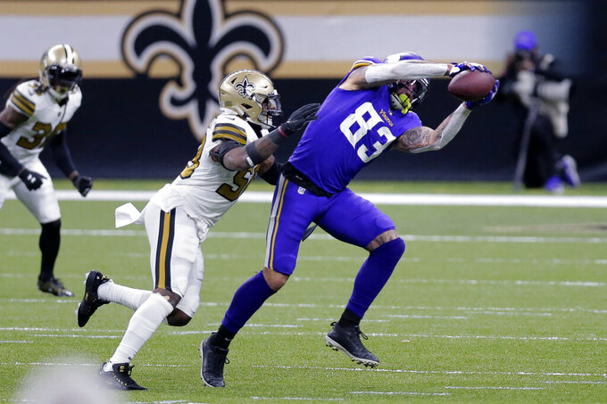 Minnesota Vikings tight end Tyler Conklin (83) pulls in a pass against New Orleans Saints outside linebacker Kwon Alexander in the first half of an NFL football game in New Orleans, Friday, Dec. 25, 2020. (AP Photo/Brett Duke)