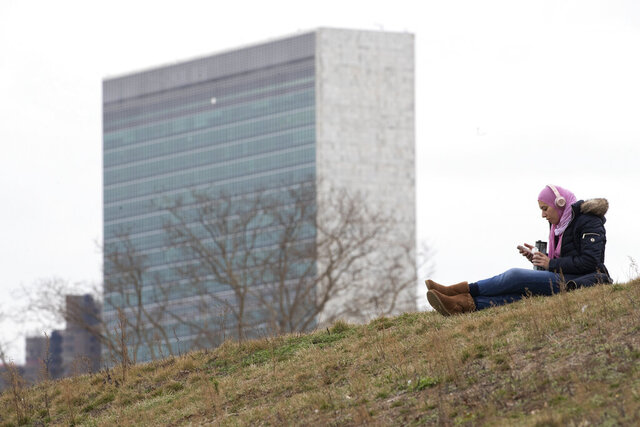 A woman listens to music at a park on Roosevelt Island, Tuesday, March 17, 2020, in New York, with a United Nations building in the background. New York State entered a new phase in the coronavirus pandemic Monday, as New York City closed its public schools, and officials said schools statewide would close by Wednesday. New York joined with Connecticut and New Jersey to close bars, restaurants and movie theaters along with setting limits on social gatherings. (AP Photo/Mary Altaffer)