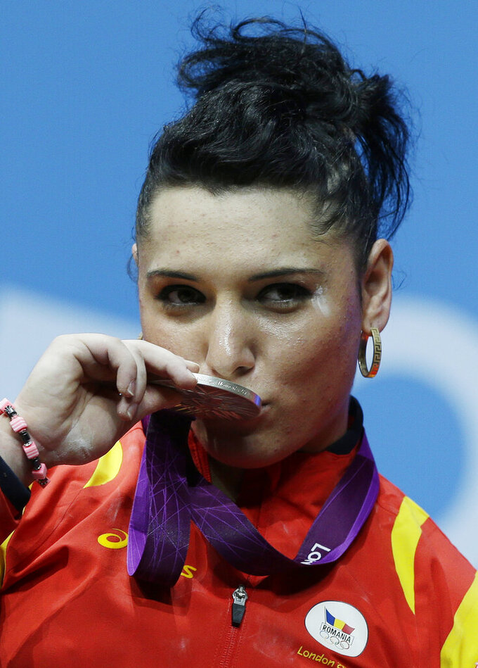 FILE - In this file photo dated Wednesday, Aug. 1, 2012, Silver medalist Roxana Cocos of Romania kisses her medal during a medals ceremony after the women's 69-kg, weightlifting competition at the 2012 Summer Olympics, in London. A culture of alleged corruption among international weightlifting officials has been detailed in a 50-page investigative report released Thursday June 24, 2021, of covered-up doping cases, with Cocos stripped of her medal years later when re-tests revealed her steroid use. (AP Photo/Hassan Ammar, FILE)