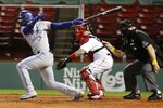 Toronto Blue Jays' Lourdes Gurriel Jr., left, follows through on an RBI-single in front of Boston Red Sox's Christian Vazquez, center, during the seventh inning of a baseball game, Saturday, Sept. 5, 2020, in Boston. (AP Photo/Michael Dwyer)