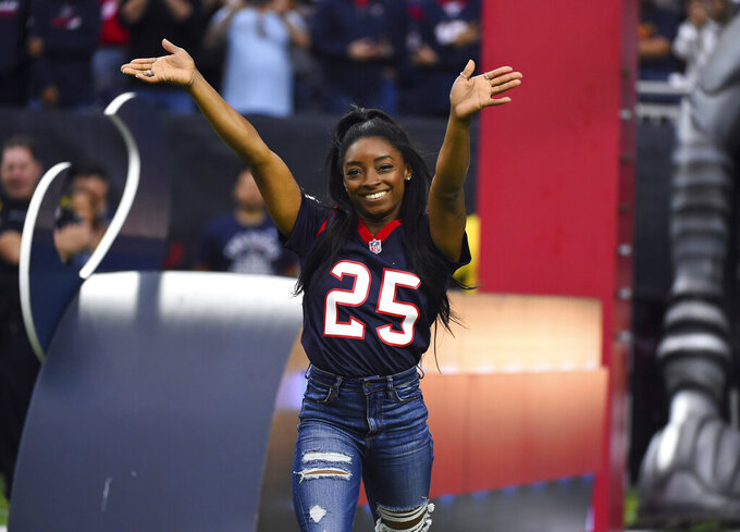 FILE - This Dec. 29, 2019 file photo shows Olympic gymnast Simone Biles leading the Houston Texans onto the field before an NFL football game against the Tennessee Titans in Houston. Biles will participate in the Class of 2020 multi-hour graduation streaming event on Facebook and Instagram on May 15.  (AP Photo/Eric Christian Smith, File)