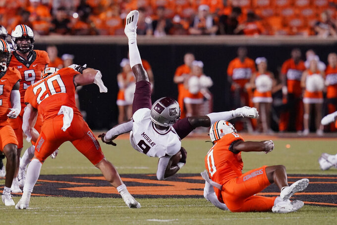 Missouri State wide receiver Jordan Murray (9) is up ended by Oklahoma State linebacker Malcolm Rodriguez (20) and cornerback Christian Holmes (0) in the second half of an NCAA college football game, Saturday, Sept. 4, 2021, in Stillwater, Okla. (AP Photo/Sue Ogrocki)