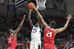 Connecticut's Akok Akok (23) goes up for two points against Sacred Heart's Tyler Thomas (22) and Jare'l Spellman (25) in the second half of an NCAA college basketball game, Friday, Nov. 8, 2019, in Storrs, Conn. (AP Photo/Stephen Dunn)