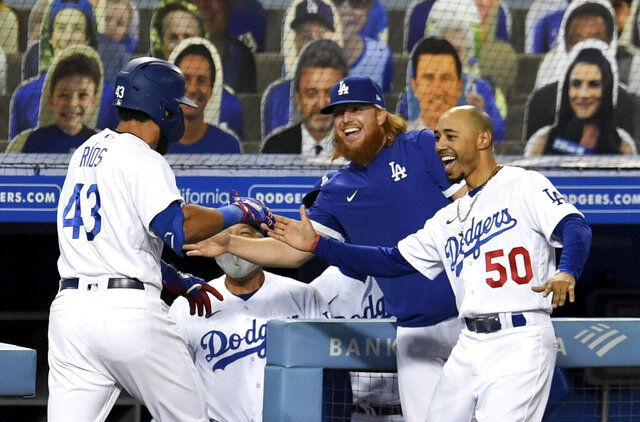 Edwin Rios #43 of the Los Angeles Dodgers celebrates with teammates Justin Turner and Mookie Betts #50 along with manager Dave Roberts after hitting a game tying solo home run against the Oakland Athletics in the eighth inning of a MLB baseball game at Dodger Stadium in Los Angeles on Wednesday, September 23, 2020. (Keith Birmingham/The Orange County Register via AP)