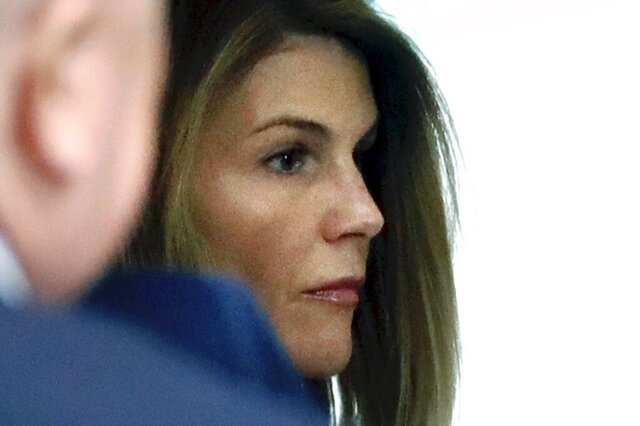 FILE - In this Aug. 27, 2019, file photo, Lori Loughlin enters through the back door at federal court in Boston for a hearing in a nationwide college admissions bribery scandal. Federal prosecutors in a legal document filed late Wednesday, April 8, 2020, denied allegations that investigators deliberately withheld and fabricated evidence to entrap actress Loughlin, her fashion designer husband Mossimo Giannulli and other prominent parents charged with cheating the college admissions process. (AP Photo/Steven Senne, File)