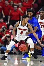 Louisville guard Lamarr Kimble (0) attempts to get past the defense of Indiana State guard Cam Bacote during the first half of an NCAA college basketball game in Louisville, Ky., Wednesday, Nov. 13, 2019. (AP Photo/Timothy D. Easley)