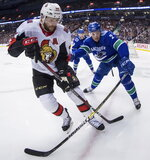 Ottawa Senators' Zack Smith, left, is checked by Vancouver Canucks' Luke Schenn during the first period of an NHL hockey game Wednesday, March 20, 2019, in Vancouver, British Columbia. (Darryl Dyck/The Canadian Press via AP)