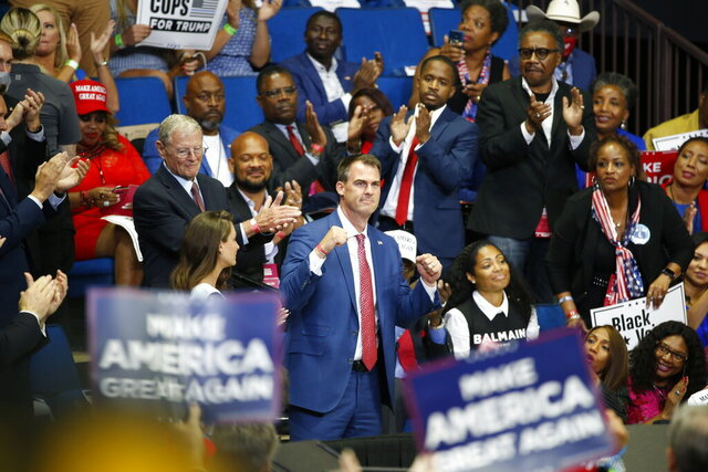 FILE - In this June 20, 2020 file photo, Oklahoma Gov. Kevin Stitt is recognized as President Donald Trump speaks during a campaign rally at the BOK Center, in Tulsa, Okla. Stitt announced Wednesday, July 15, 2020, that he's tested positive for the coronavirus and that he is isolating at home. The first-term Republican governor has backed one of the country's most aggressive reopening plans, has resisted any statewide mandate on masks and rarely wears one himself. (AP Photo/Sue Ogrocki, File)