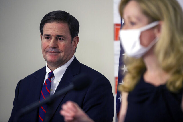 Gov. Doug Ducey listens as Arizona Department of Health Services Director Cara Christ speaks during a press conference regarding the COVID-19 pandemic, Thursday, Aug. 13, 2020, at the Arizona Department of Health Services in Phoenix. (Sean Logan/The Arizona Republic via AP)