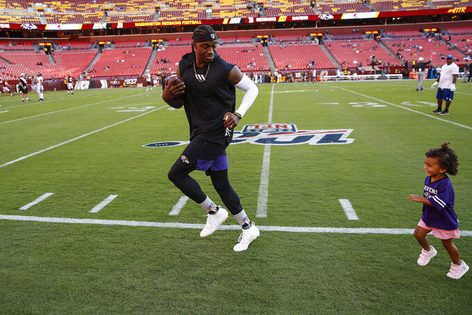 Baltimore Ravens quarterback Robert Griffin III runs with his daughter Gloria Griffin, 2, before an NFL preseason football game against the Washington Redskins, Thursday, Aug. 29, 2019, in Landover, Md. (AP Photo/Alex Brandon)