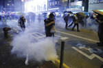 Protestors run for cover from tear gas shells during a protest in Mong Kok, Hong Kong on Friday, Sept. 6, 2019. The ratings agency Fitch on Friday cut Hong Kong's credit rating and warned that conflict with anti-government protesters was hurting the image of its business climate. (AP Photo/Kin Cheung)