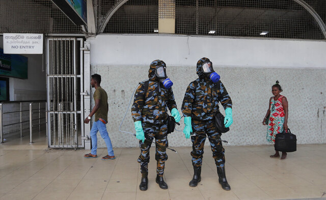 Sri Lankan government soldiers in protective clothes prepare to spray disinfectant inside a railway station in Colombo, Sri Lanka, Wednesday, March 18, 2020. For most people, the new coronavirus causes only mild or moderate symptoms. For some, it can cause more severe illness, especially in older adults and people with existing health problems. (AP Photo/Eranga Jayawardena)