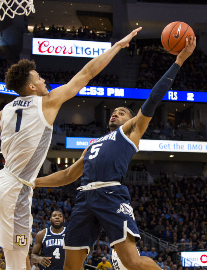 Villanova guard Phil Booth, right, goes up for a basket against Marquette forward Brendan Bailey, left, during the second half of an NCAA college basketball game Saturday, Feb. 9, 2019, in Milwaukee. Marquette defeated Villanova 66-65. (AP Photo/Darren Hauck)