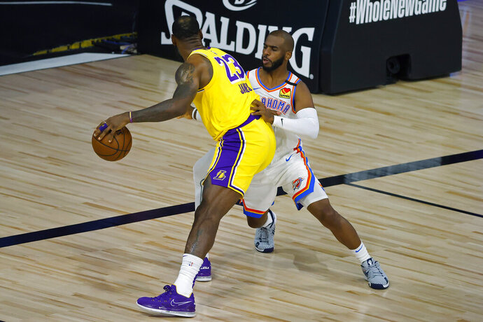 Los Angeles Lakers' LeBron James (23) is defended by Oklahoma City Thunder's Chris Paul during the first half of an NBA basketball game Wednesday, Aug. 5, 2020, in Lake Buena Vista, Fla. (Kevin C. Cox/Pool Photo via AP)