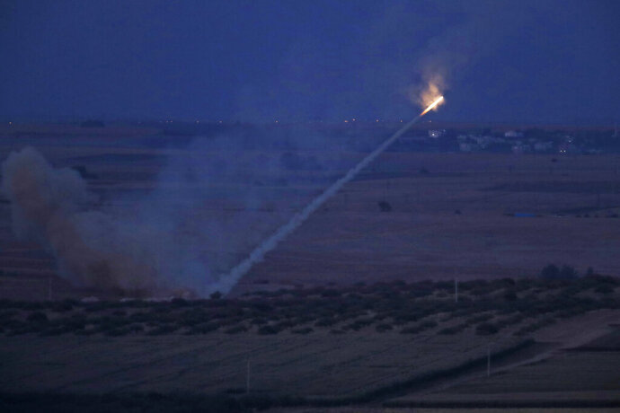 In this photo taken from the Turkish side of the border between Turkey and Syria, in Ceylanpinar, Sanliurfa province, southeastern Turkey, Turkish forces fire rockets towards targets in Ras al-Ayn, Syria, Tuesday, Oct. 15, 2019. (AP Photo/Lefteris Pitarakis)