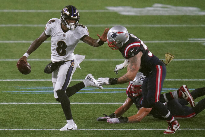 Baltimore Ravens quarterback Lamar Jackson, left, tries to elude New England Patriots defensive end John Simon in the second half of an NFL football game, Sunday, Nov. 15, 2020, in Foxborough, Mass. (AP Photo/Charles Krupa)