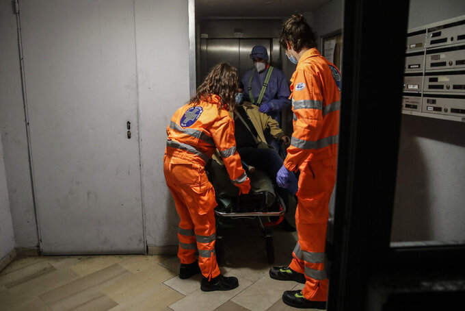 From left, medical volunteer Beatrice Ammattatiello, medical staffers Paolo Pozzoli and Andrea Arosio, right, carry a suspected Covid patient in the hall of an apartment building during their shift with the emergency White Cross ambulance, in Cinisello Balsamo, near Monza, Italy, Thursday, Nov. 19, 2020. The city of Monza north of Milan is best known for its Formula 1 racetrack. In 2020, it has been the ambulance service that has been doing most of the racing. Over three days that an Associated Press photographer traveled on night calls with an ambulance service, the Monza-Brianza province of some 875,000 bordering Milan added 2,500 new cases, part of Italy's new epicenter in the Lombardy region. (AP Photo/Luca Bruno)