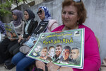 """A Palestinian woman carries a poster with pictures of the six Palestinian prisoners who escaped from an Israeli jail that says """"heroes of the freedom tunnel,"""" during a protest in the West Bank city of Ramallah, Tuesday, Sept. 14, 2021. The cinematic escape of six prisoners who tunneled out of an Israeli penitentiary shone a light on Israel's mass incarceration of Palestinians, one of the many bitter fruits of the conflict. (AP Photo/Nasser Nasser)"""