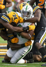 North Texas running back Isaiah Johnson, center, is engulfed by Missouri linemen during the third quarter of an NCAA college football game Saturday, Oct. 9, 2021, in Columbia, Mo. (AP Photo/L.G. Patterson)