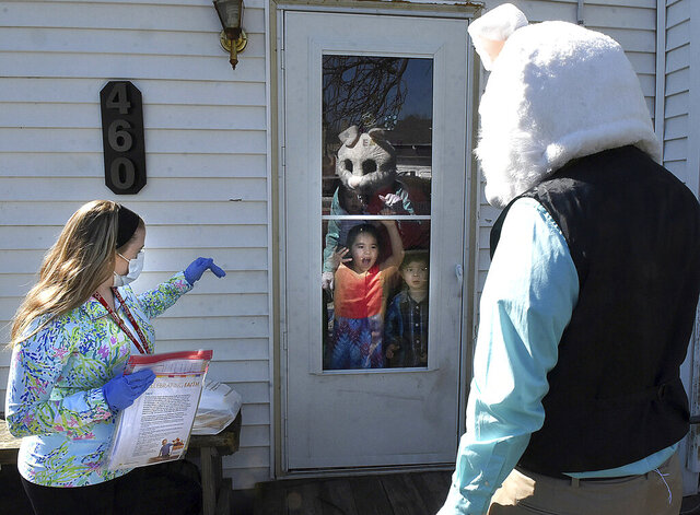Kindergarten teacher Ainsley Henderson, left, and the Easter Bunny wave goodbye to St. Rose School kindergarten student Anica Ramirez, 5, as teachers and staff drop off student work, Thursday, April 2, 2020, in Lima, Ohio. St. Rose teachers and staff have been working on the best way to pick up student work and provide them with materials for the next several weeks, as schools are closed due to the coronavirus pandemic. (Craig J. Orosz/The Lima News via AP)