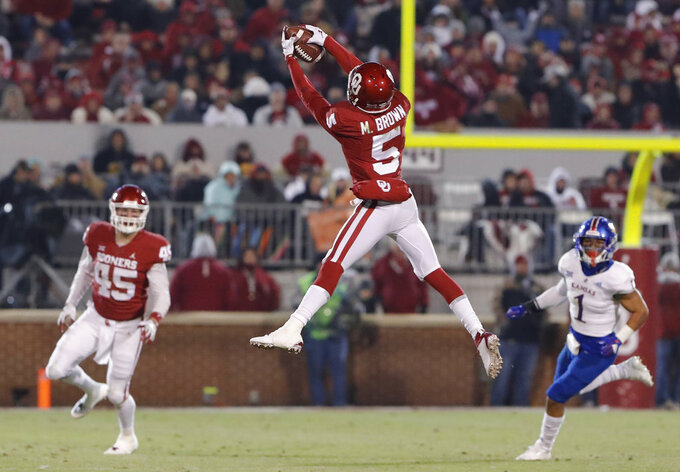 Oklahoma wide receiver Marquise Brown (5) makes a catch as Kansas safety Bryce Torneden (1) and Oklahoma fullback Carson Meier (45) looks on during the second half of an NCAA college football game in Norman, Okla., Saturday, Nov. 17, 2018. Oklahoma won 55-40. (AP Photo/Alonzo Adams)
