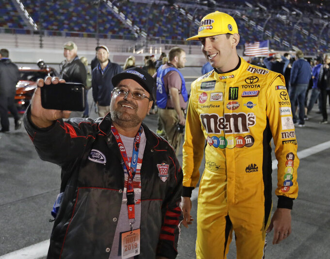 Kyle Busch, right, poses for a selfie photo with a race fan before the first of two qualifying auto races for the NASCAR Daytona 500 at Daytona International Speedway, Thursday, Feb. 14, 2019, in Daytona Beach, Fla. (AP Photo/John Raoux)