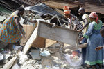 Local people attend the scene after a building collapsed in Lagos, Nigeria, Thursday March 14, 2019. Search and rescue work continues in Nigeria a day after a building containing a school collapsed with scores of children said to be inside. A National Emergency Management Agency spokesman late Wednesday said 37 people had been pulled out alive, with eight bodies recovered from the ruins. (AP Photo/Sunday Alamba)