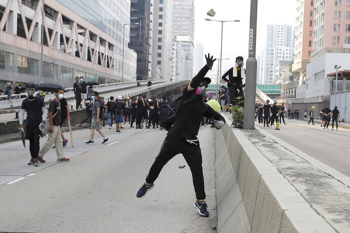 A protestor throws a block towards police as they clash during a protest in Hong Kong, Saturday, Aug. 24, 2019. Hong Kong protesters skirmished with police on Saturday as chaotic scenes returned to the summer-long protests for the first time in more than a week. (AP Photo/Kin Cheung)