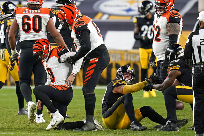 Cincinnati Bengals quarterback Joe Burrow (9) is helped up by center Trey Hopkins after being sacked by Pittsburgh Steelers outside linebacker T.J. Watt (90) during the second half of an NFL football game, Sunday, Nov. 15, 2020, in Pittsburgh. (AP Photo/Keith Srakocic)