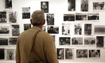 FILE - In this May 18, 2009 file photo, a man looks at prints from the Looking In: Robert Frank's