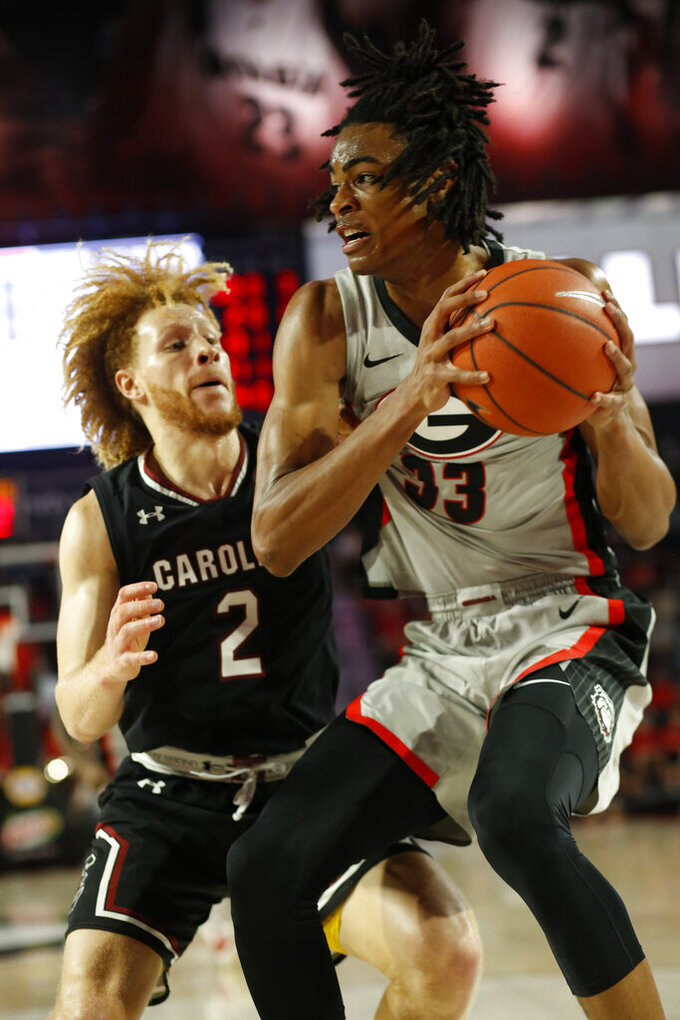 Georgia forward Nicolas Claxton (33) tries to get by South Carolina guard Hassani Gravett (2) during an NCAA college basketball game  in Athens, Ga., on Saturday, Feb. 2, 2019.  (Joshua L. Jones/Athens Banner-Herald via AP)