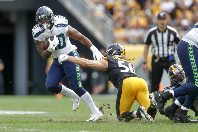 Seattle Seahawks running back Rashaad Penny (20) breaks away from Pittsburgh Steelers linebacker Anthony Chickillo (56) on his way to a long touchdown run in the second half of an NFL football game, Sunday, Sept. 15, 2019, in Pittsburgh. (AP Photo/Don Wright)