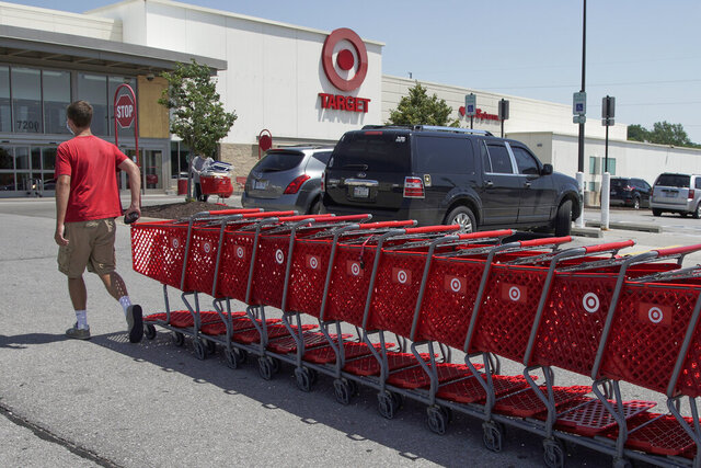 FILE - A Target employee returns shopping carts from the parking lot, in Omaha, Neb., Tuesday, June 16, 2020. Target Corp. says it's permanently increasing starting hourly wages for its workers to $15 beginning July 5, several months ahead of schedule.   (AP Photo/Nati Harnik)