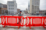 A man walks by orange fencing set up outside the Pennsylvania State Capitol in Harrisburg, Pa., Thursday, Jan. 14, 2021, in advance of Joe Biden's Presidential Inaugural in Washington D.C. on Jan. 20. (Mark Pynes/The Patriot-News via AP)