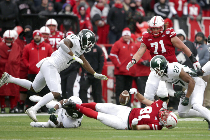 Nebraska wide receiver Kade Warner (81) fumbles the ball for a turnover after a hit by Michigan State linebacker Andrew Dowell, bottom left, as safety Khari Willis (27) and linebacker Tyriq Thompson (17) close in, during the first half of an NCAA college football game in Lincoln, Neb., Saturday, Nov. 17, 2018. (AP Photo/Nati Harnik)