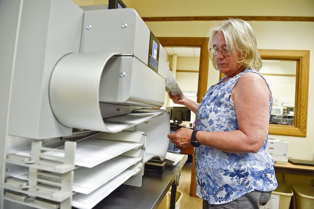Peggy Kerins runs voted ballots through a tabulation machine during Montana's primary election Tuesday, June 2, 2020 in the City-County Building Tuesday in Helena. Montana's June 2 primary is being held by mail because of the coronavirus.  (Thom Bridge/Independent Record via AP)