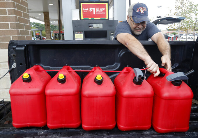 """Paul Villagomez secures filled gas containers in his truck as he prepares for Tropical Storm Nicholas, Monday, Sept. 13, 2021, in Kingwood, Texas. """"I'm just trying to be prepared,"""" Villagomez said. """"I'm actually surprised there aren't more people filling up."""" (Jason Fochtman/Houston Chronicle via AP)"""
