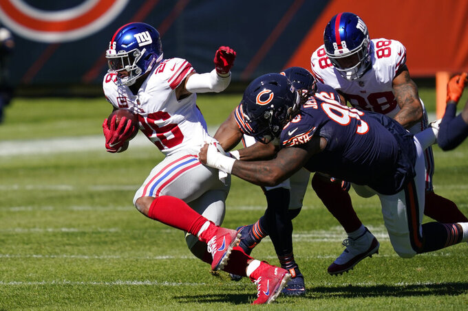 New York Giants running back Saquon Barkley (26) tries to break free from Chicago Bears defensive tackle John Jenkins (90) during the first half of an NFL football game in Chicago, Sunday, Sept. 20, 2020. (AP Photo/Charles Rex Arbogast)