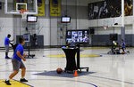 In this photo taken on Tuesday, June 9, 2020, coaches including VeAnne Navarro, left, work with virtual students at Golden State Warriors basketball camp in Oakland, Calif. The Warriors had to adapt their popular youth basketball camps and make them virtual given the COVID-19 pandemic. (AP Photo/Ben Margot)