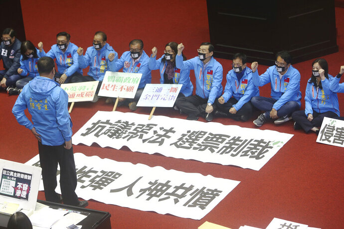 FILE - In this Dec. 31, 2019, file photo, legislators of KMT or Nationalist Party protest the Anti-infiltration Bill which is meant to criminalize political activities back or funded by mainland China, with slogans reading ''Protest against a bad law, Sanction by Votes. Neck Bomb, Be hated by both man and God'' on the legislature floor in Taipei, Taiwan. Taiwan's ruling party is crying foul over alleged Chinese attempts to sway the self-governing island's presidential election on Saturday, Jan. 11, 2020. The Democratic Progressive Party, known as the DPP, rushed through a law banning