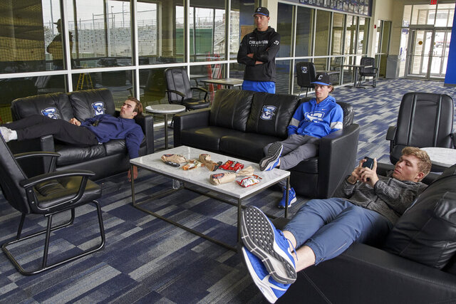 In this March 13, 2020 photo, Creighton NCAA college baseball pitchers Ben Dotzler, top center, and Tommy Steier, second right, watch President Trump declare a national emergency to combat the coronavirus pandemic, in the player lounge in Omaha, Neb. Dotzler was supposed to be in the bullpen at TD Ameritrade Park this weekend readying himself to pitch against Northern Colorado, Everything changed for hm and thousands of other college athletes when the NCAA announced March 12, 2020, it was canceling all spring sports championships, along with remaining winter championships, as a precaution against the spread of the new coronavirus.  (AP Photo/Nati Harnik)