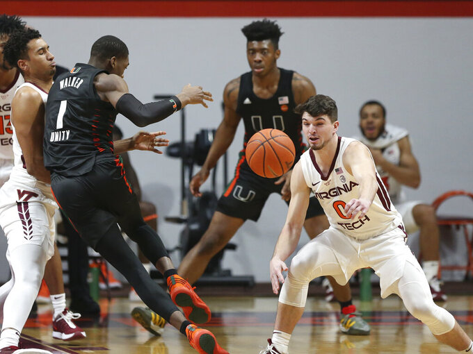 Virginia Tech's Hunter Cattoor (0)breaks up a drive by Miami's Anthony Walker (1) during the first half of an NCAA college basketball game, Tuesday, Dec. 29, 2020 in Blacksburg, W.Va. (Matt Gentry/The Roanoke Times via AP, Pool)