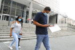 Luis Solis, right, checks a cell phone as he walks with his wife Damaris Solis, left, and their son, Wilder Solis, 6, after being turned away at the federal building while attempting a check-in, Monday, July 13, 2020, in Baltimore. The Solis', along with many other people, had an appointment to check-in with immigration officials, but where given a notice to return on July 28th. Some immigration courts across the country have reopened after closing because of the coronavirus pandemic. (AP Photo/Julio Cortez)
