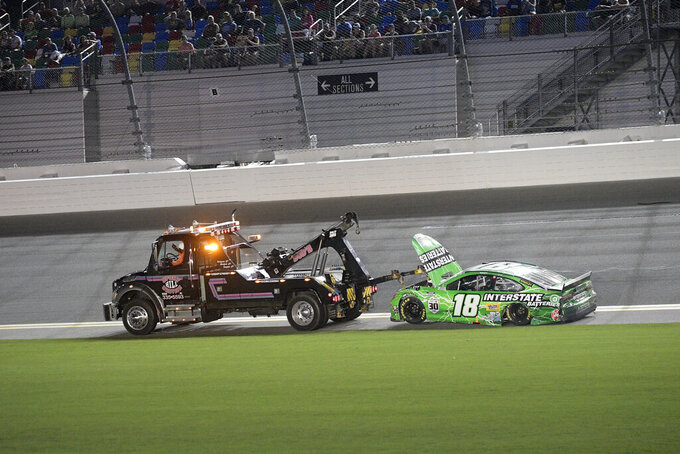 Kyle Busch (18) is towed off the track after getting involved in a collision during a NASCAR Cup Series auto race at Daytona International Speedway, Saturday, Aug. 28, 2021, in Daytona Beach, Fla. (AP Photo/Phelan M. Ebenhack)