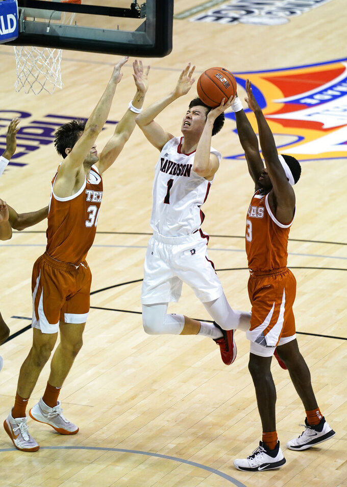 Davidson forward Hyunjung Lee (1) drives the ball to the basket between Texas forward Brock Cunningham (30) and guard Courtney Ramey (3) in the second half of an NCAA college basketball game in the Maui Invitational tournament, Monday, Nov. 30, 2020 in Asheville, N.C. Texas won 78-76. (AP Photo/Kathy Kmonicek)