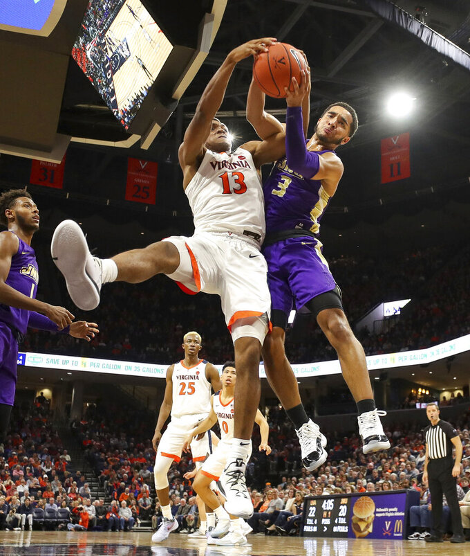 Virginia guard Casey Morsell (13) fights for a rebound with James Madison guard Deshon Parker (3) during an NCAA college basketball game in Charlottesville, Va., Sunday, Nov. 10, 2019. Virginia won 65-34. (AP Photo/Andrew Shurtleff)
