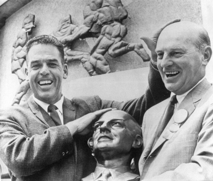 FILE - In this Aug. 5, 1967, file photo, Pro Football Hall of Famer Otto Graham, left, presents a bust to Paul Brown during Brown's induction ceremony at the Pro Football Hall of Fame in Canton, Ohio. In Ohio, Brown was synonymous with football. He led Ohio State to its first national title before becoming head coach of the Browns, who won four All-America Football Conference titles and then three in the NFL under Brown.  (AP Photo/Julian C. Wilson, File)