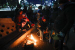 In this Sept. 4, 2019 photo, people warm up near a fire as they camp and protest outside the Social Development Ministry in Buenos Aires, Argentina. Social organizations are calling a food emergency and asking the government to provide food to the needy. (AP Photo/Natacha Pisarenko)